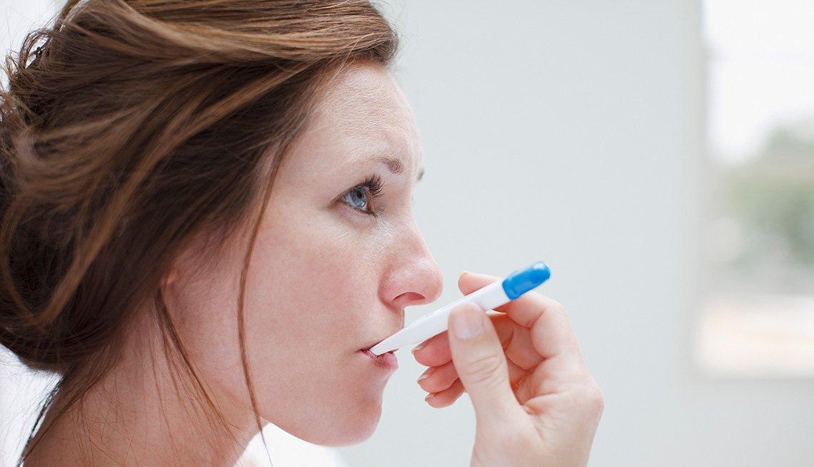 Mujer midiéndose la temperatura en la boca con un termómetro