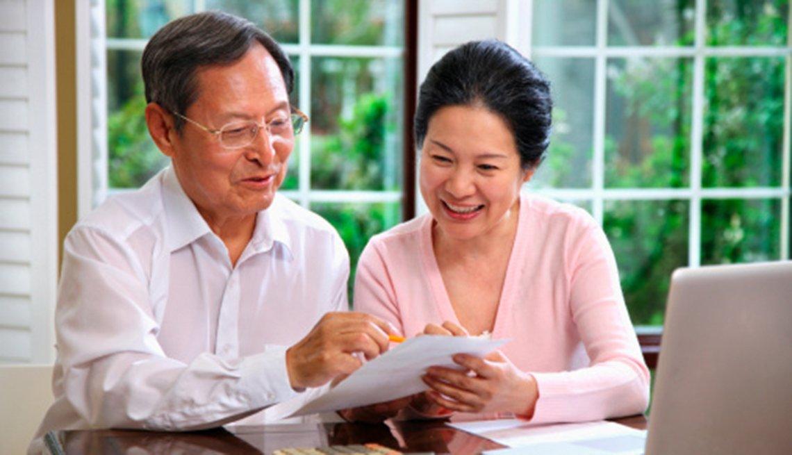 Pareja asiática de edad mediana mirando cuentas en su casa