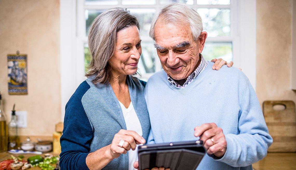 Una pareja de adultos mayores usando su laptop en la cocina