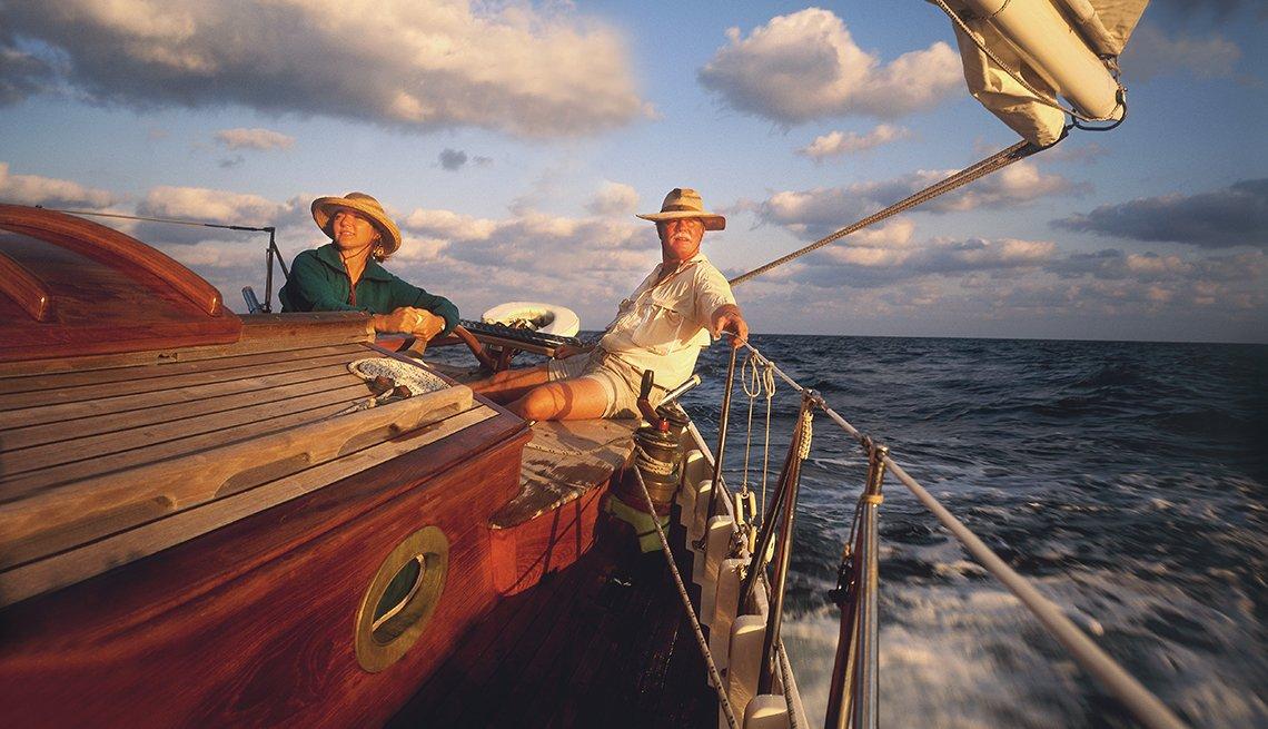Una pareja en un bote de vela mientras el sol se pone