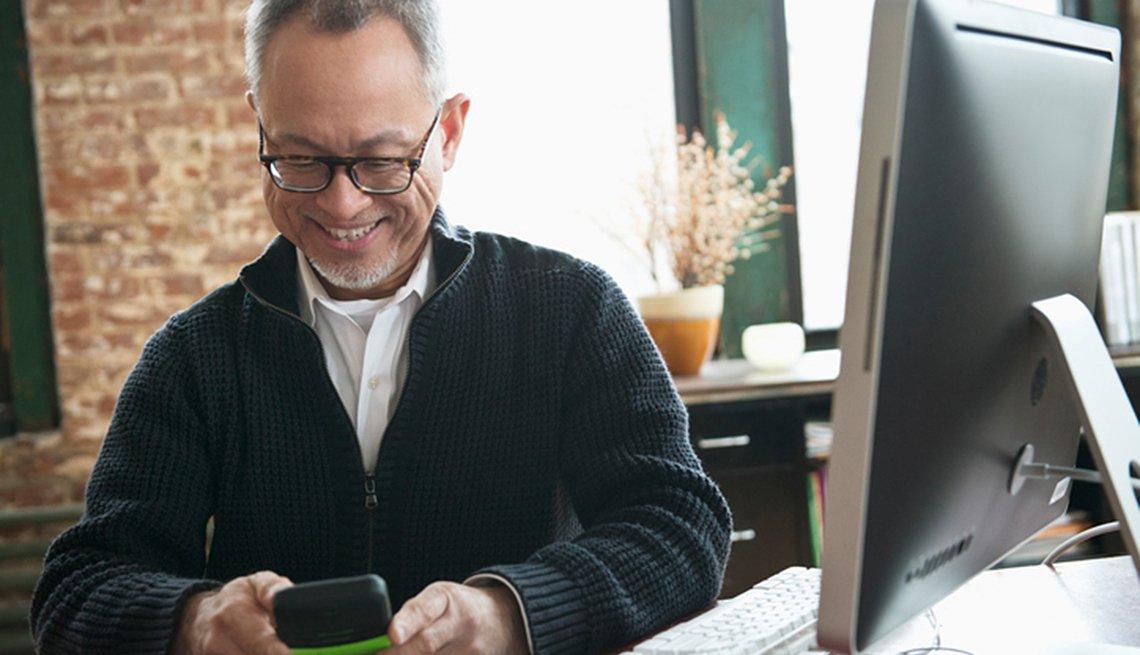 Hombre de mediana edad usando un teléfono celular en su oficina