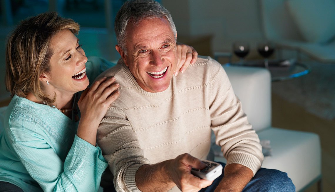 Mature couple smiling watching television