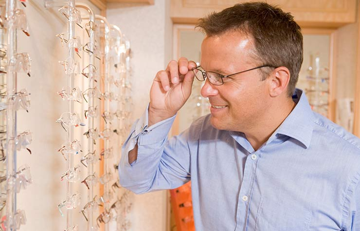AARP membership discount Man trying on eyeglasses at optometrists smiling