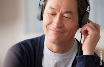 Mature man wearing headphones, Hearing Center for Oct Protect Your Hearing Month