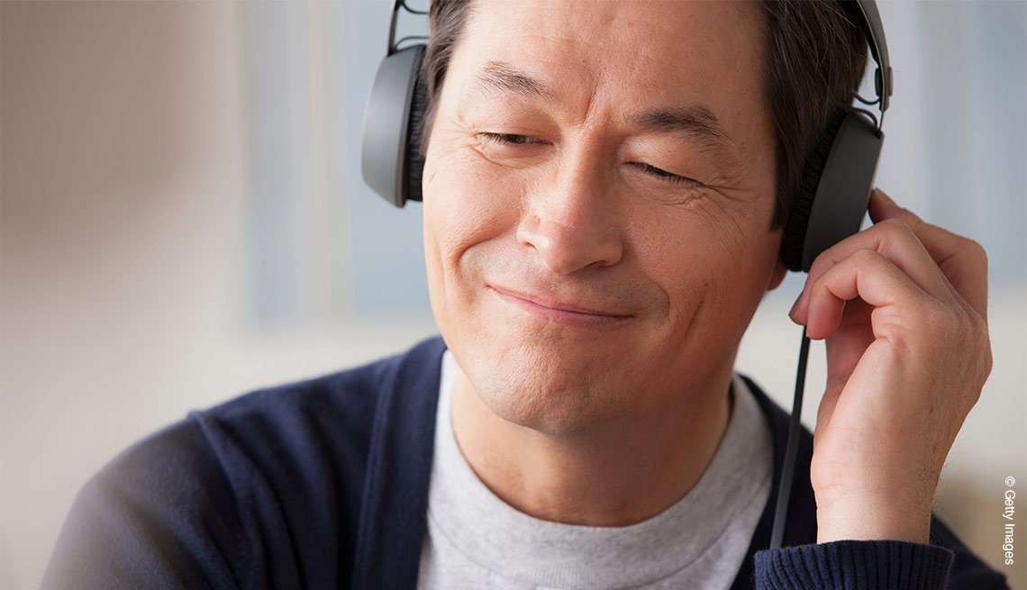 Un asiático escuchando música con sus auriculares