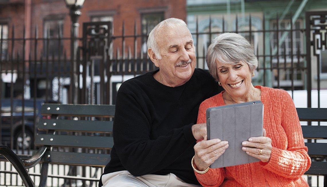Una pareja de adultos mayores mira su iPad sentados en un banco en la calle