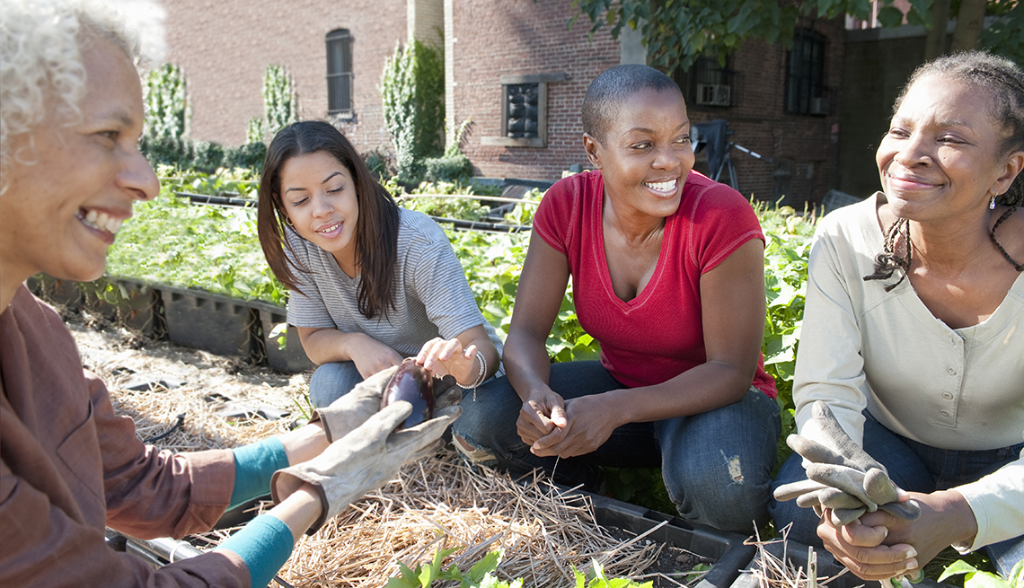 A group of women meet in a community garden