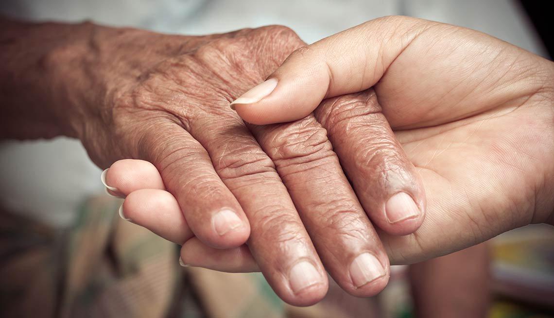 Una mano joven sostiene la mano de una persona mayor
