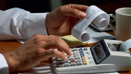 A person uses a calculator to go through bills