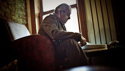 An older man reads through books in his living room.