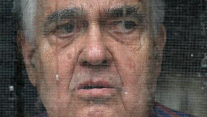 A poor man peers out his screen door in Maine