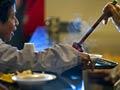 Voluntarios sirvendo una sopa: Campaña de AARP para erradicar el hambre en América