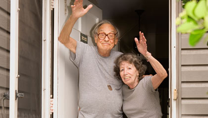 A senior couple waving in the door of their home