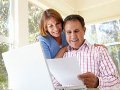 Couple working on laptop with paperwork, Estate planning
