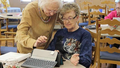 Connecting to Community volunteer helps a partipant use a tablet