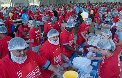 Volunteers pack meals during AARP Foundation's