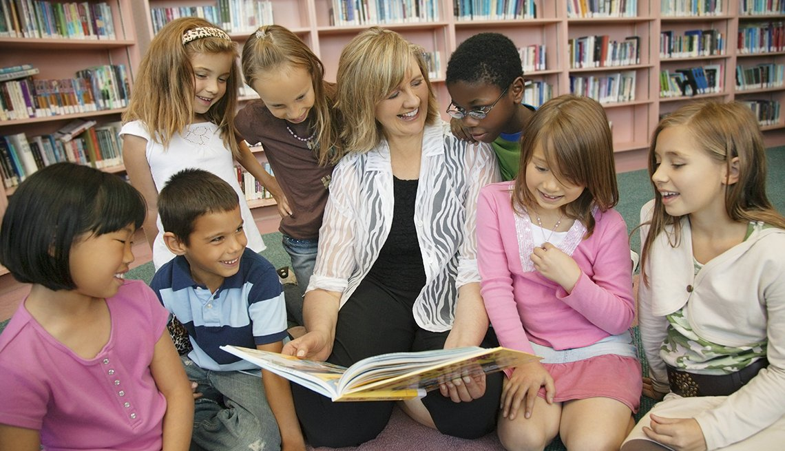 Woman Reading to Students, Library Bookshelves, Looking at Kids, AARP Experience Corps Stories From Researchers