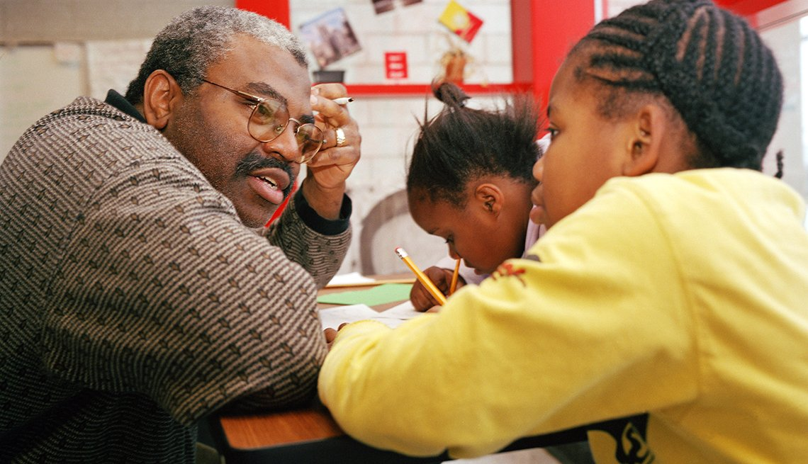 A Man Tutors Students in School, AARP Foundation Experience Corps
