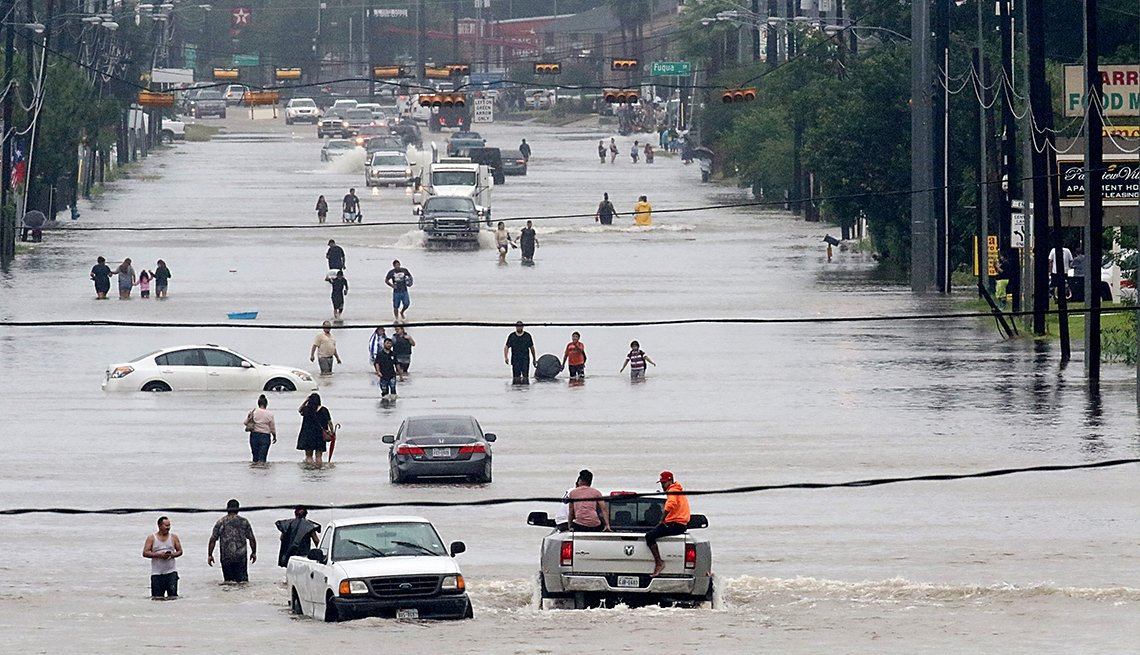 People walk through the flooded waters of Telephone Rd. in Houston on August 27, 2017 as the US fourth city city battles with tropical storm Harvey and resulting floods.