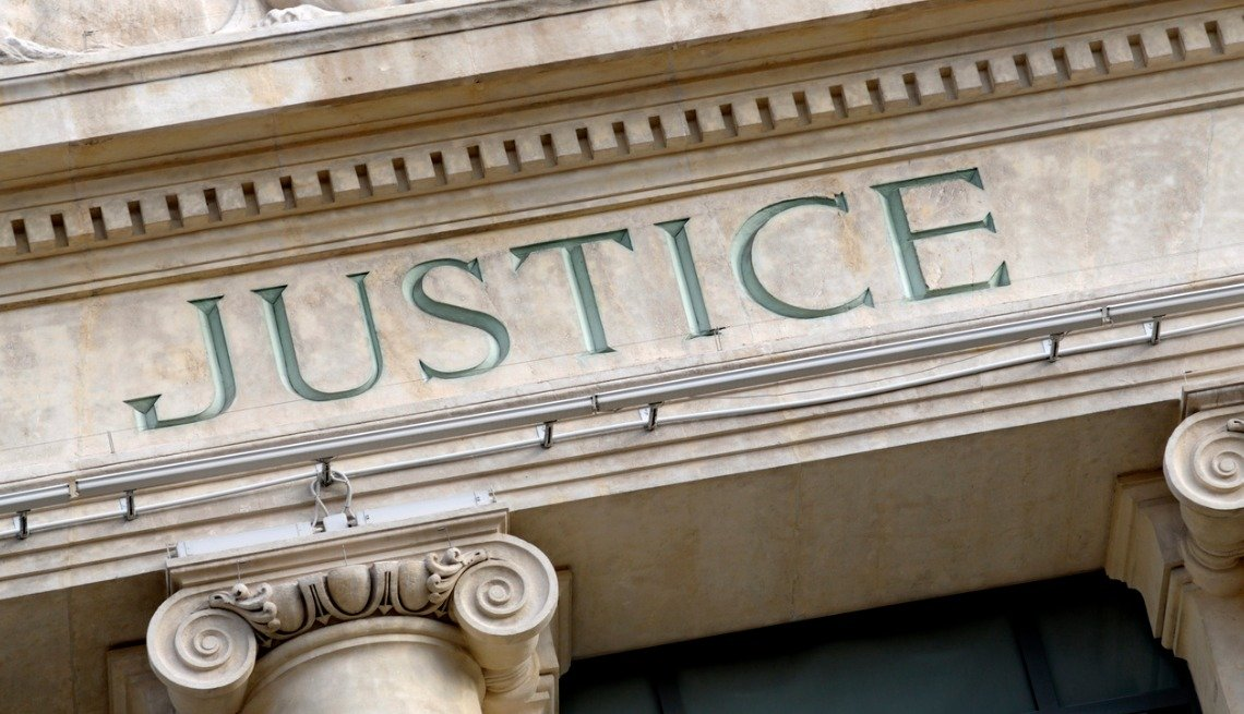 Justice sign over courthouse entrance