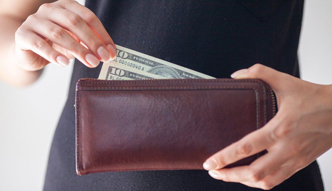 a woman taking a ten dollar bill from her wallet
