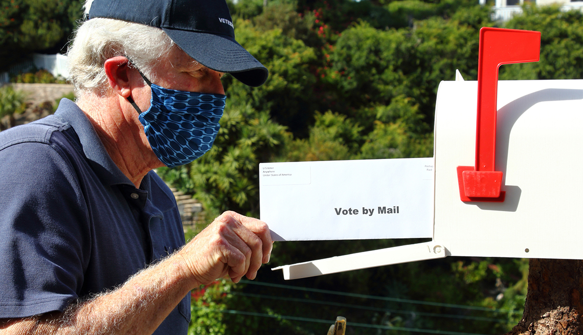 a man wearing a face mask is putting an envelope that says vote by mail on it into a mailbox