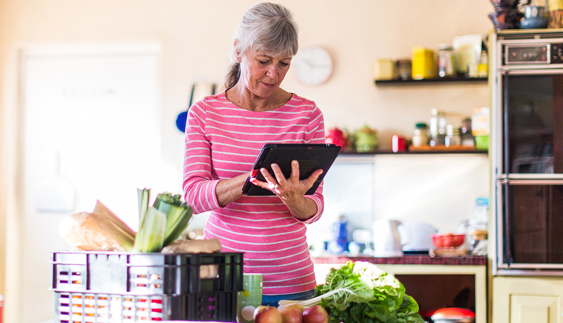 A woman standing in her kitchen next to groceries using a tablet