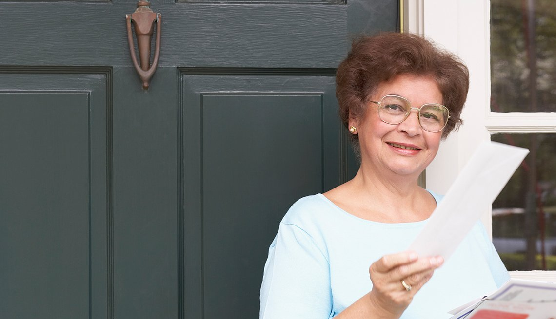 Mature woman, holding mail, outside house, AARP Foundation, Guide to Public Benefits