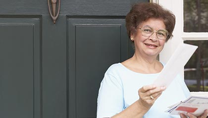 Portrait of a senior woman holding her mail - Your Guide to Public Benefits