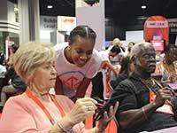 Atlanta Life@50+ event, Anijarae Dade helps seniors use tablet