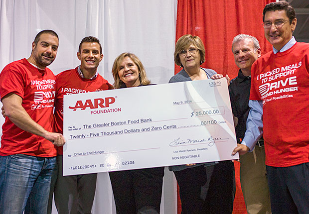 Kitchen Cousins stars Anthony Carrino and John Colaneri and others with a big check for the Greater Boston Food Bank during the AARP Life@50+ event in Boston.