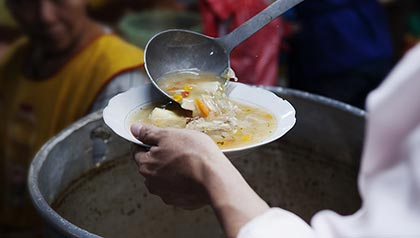 A woman serves soup, learn about hunger, AARP Foundation