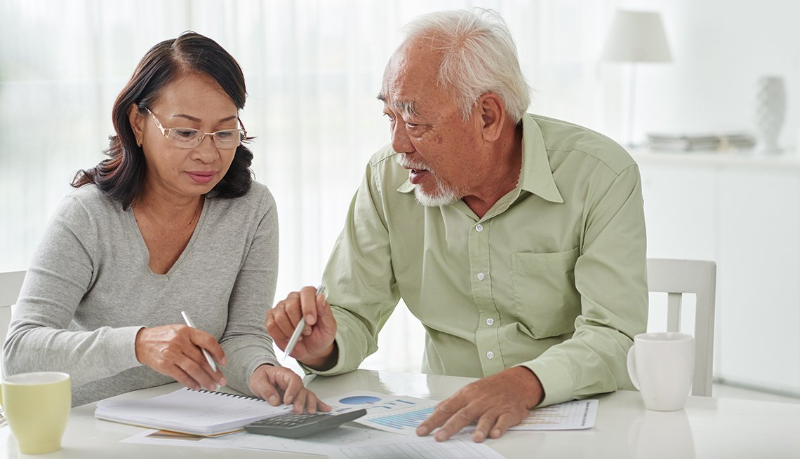 Senior Asian business couple discussing financial documents, Finances 50 plus, AARP Foundation
