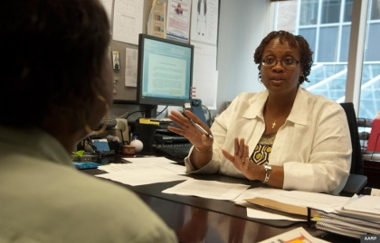 Woman at desk talking to client, AARP Legal Counsel for the Elderly