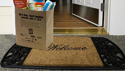 Welcome mat with paper bag at front door, Stamp Out Hunger