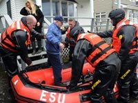 Police evacuate a man from Breezy Point in the aftermath of Hurricane Sandy. One year later, recovery continues. (Debbie Egan-Chin/New York Daily News/Getty Images)