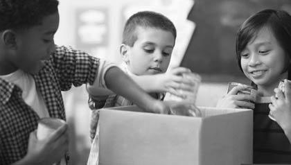 Niños organizan una caja de comida para una unidad de alimentación escolar, Campaña de AARP Drive To En Hunger