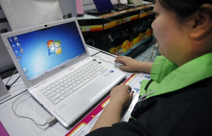 A woman uses a laptop with the Microsoft Windows 7 system at a store.