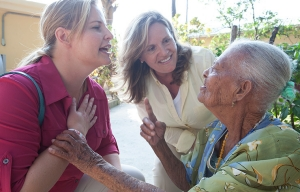 Debra Whitman and AARP Foundation President Lisa Ryerson visit Mirta Pierre, 90, at the St. Vincent de Paul nursing home in Leogane, Haiti.
