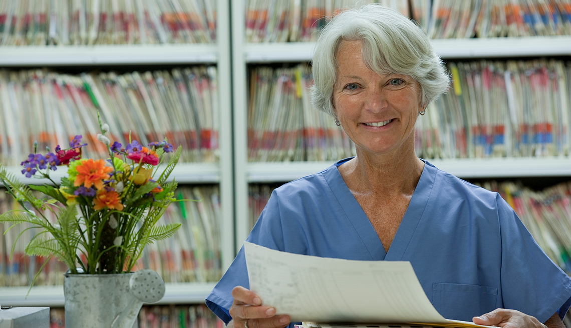 Mature woman, reviewing files, medical office, AARP Foundation, Back to Work 50 plus