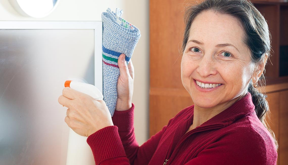 Smiling mature woman, cleaning glass, Explore your options, Work for Yourself 50+, AARP Foundation