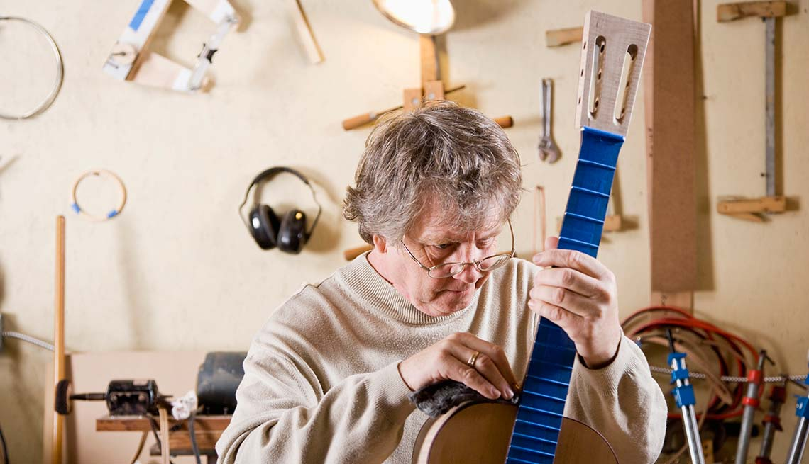 Mature man working on guitar, Work for Yourself 50+, AARP Foundation