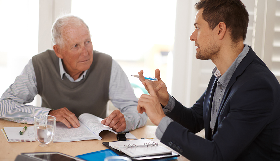 Senior man talking with younger man at table, AARP Foundation, Elderwatch