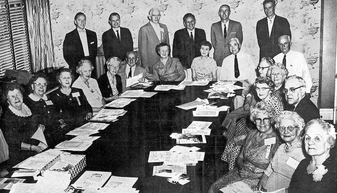 item 1 of Gallery image - A group of people gathered around a table for an AARP meeting.
