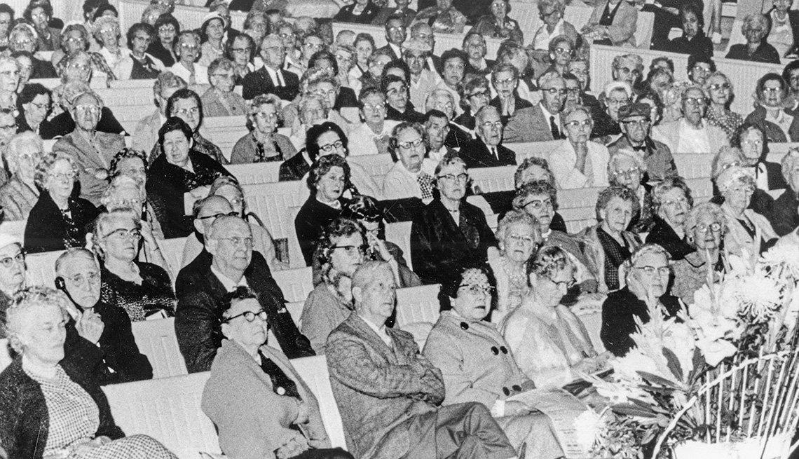 item 9, Gallery image. Muchedumbre en un auditorio pone atención a una presentación que ancontece.