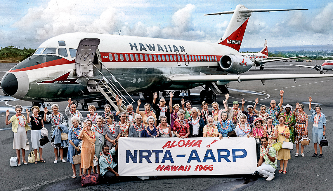 A group of people standing outside a Hawaiian plane with banner reading