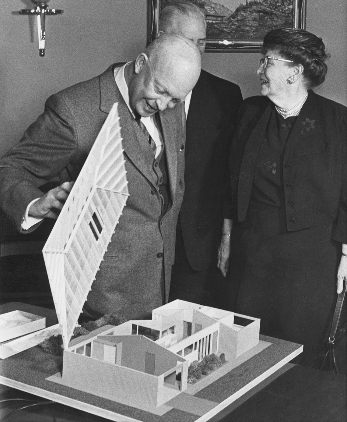 """President Eisenhower examines a scale model of the """"House of Freedom,"""" with Dr. Andrus in the background."""
