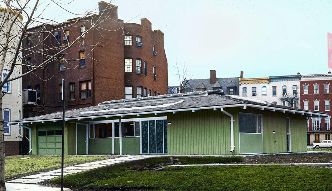 item 2 of Gallery image - Casa modesta, verde, de un nivél y rodeada de edificios más altos.