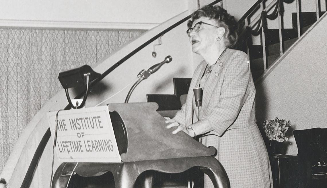 """item 3 of Gallery image - Señora mayor de pié detrás de un podio con las palabras """"The Institute of Lifetime Learning""""."""