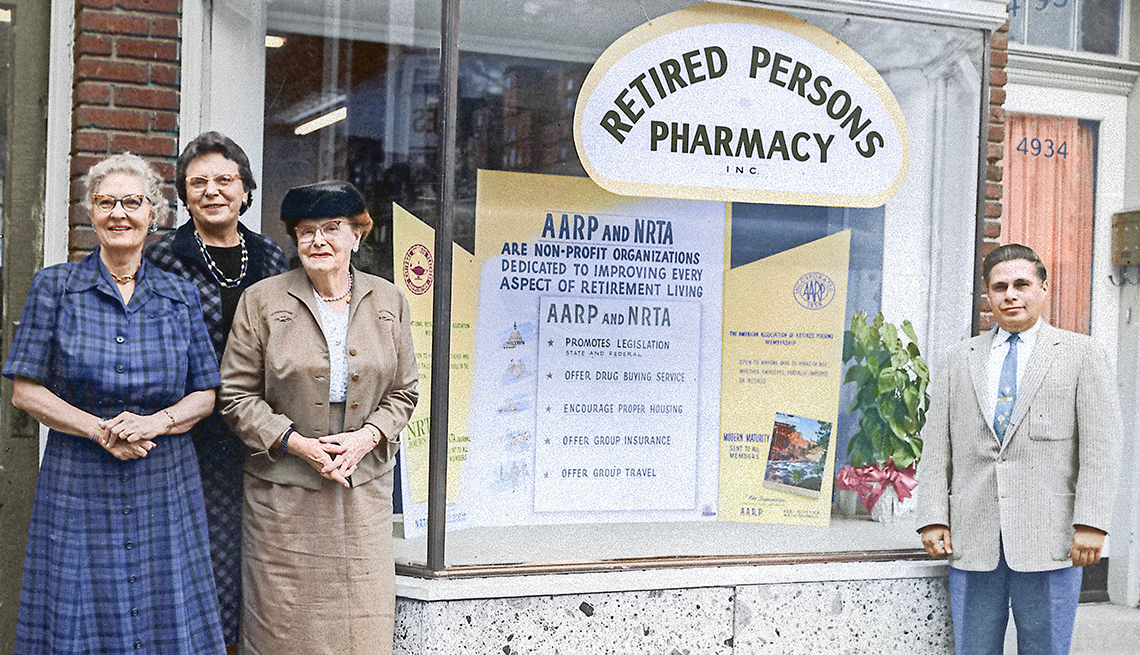 "A group of people stand in front of the ""Retired Persons Pharmacy."""